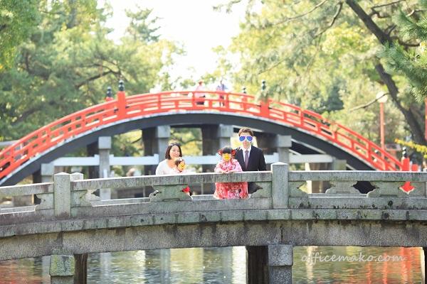神社の橋の上で家族写真を撮っている写真です