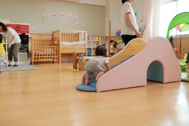 保育園で滑り台にのぼる赤ちゃんの写真