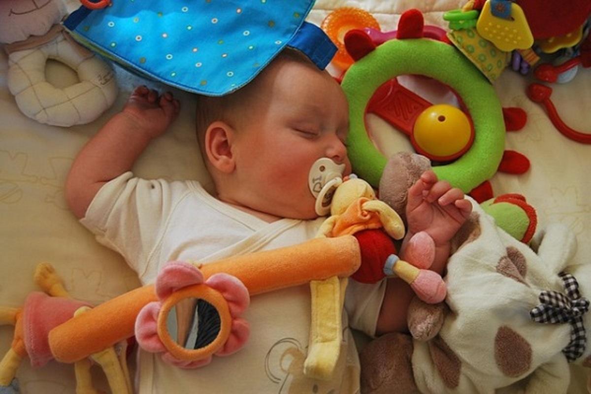 寝ている赤ちゃんとおもちゃの写真