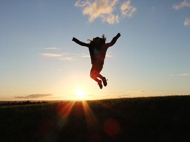 夕日とジャンプしている男性の写真