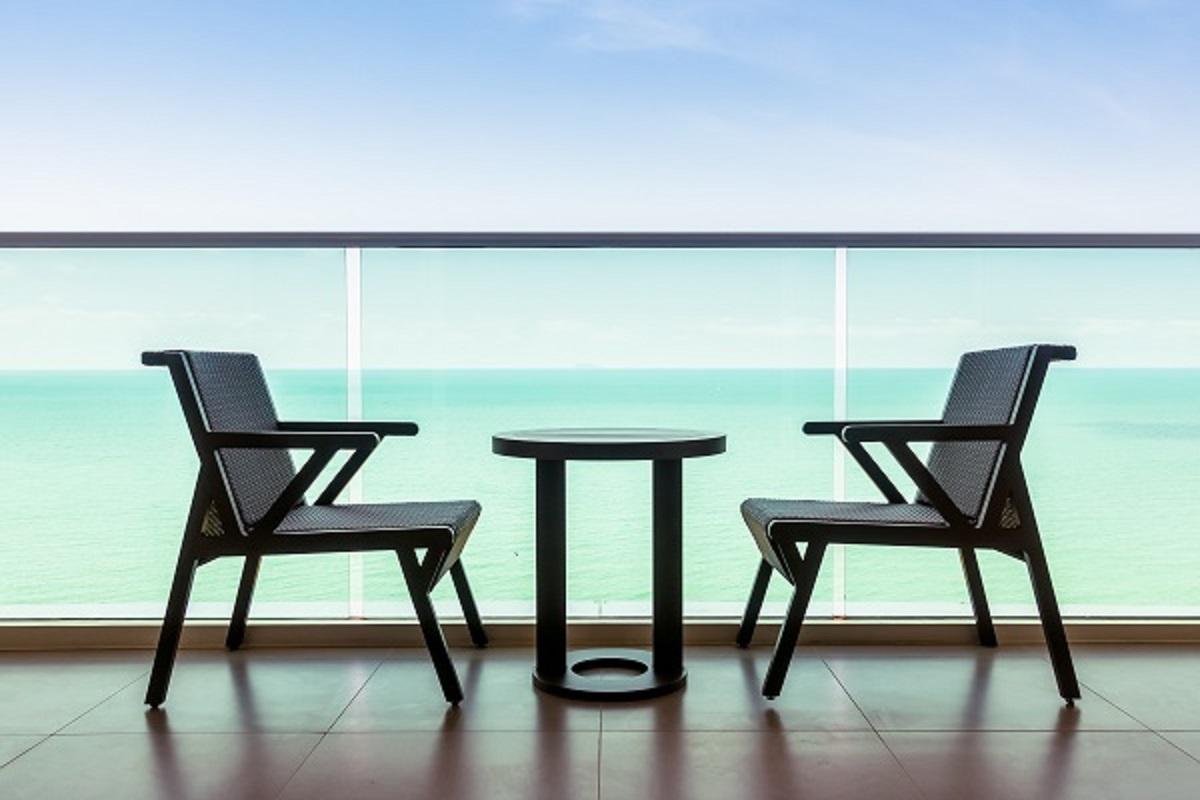 海の見えるテラスにテーブルと椅子が置いてある画像