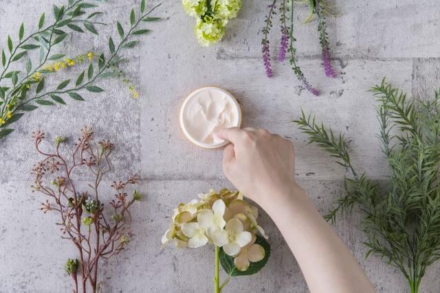オーガニックの植物に囲まれたクリームに、指を入れている画像