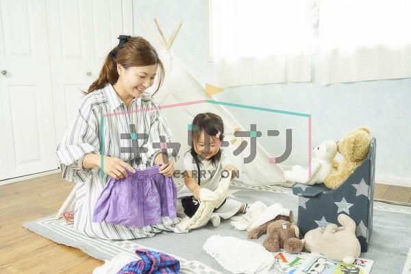 お母さんと女の子が洋服の整理をしている画像