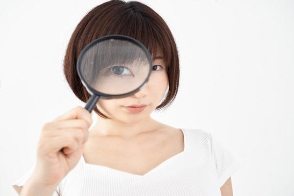 虫眼鏡を覗く女性の画像