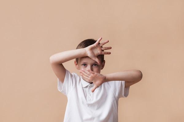 顔の前に手を広げている男の子の画像