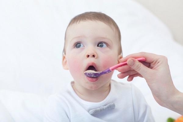 スプーンにのった離乳食を食べる赤ちゃんの画像