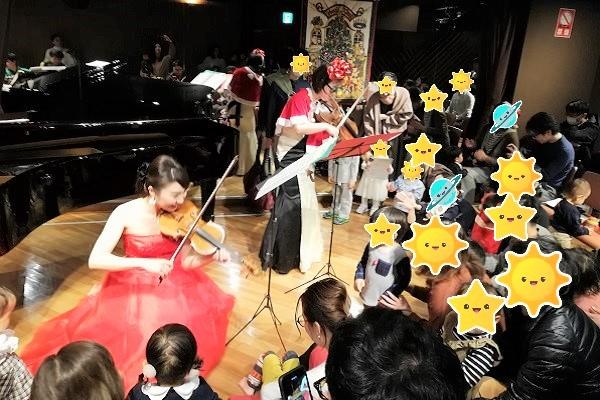 子供達の目の前でバイオリンを弾く女性の画像