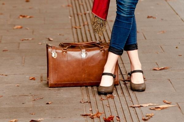 旅行かばんと女性の脚の画像
