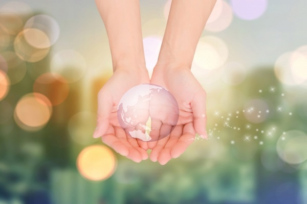 地球を両手で包んでいるイメージの画像