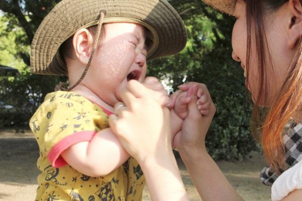 泣いている赤ちゃんと保育士の画像
