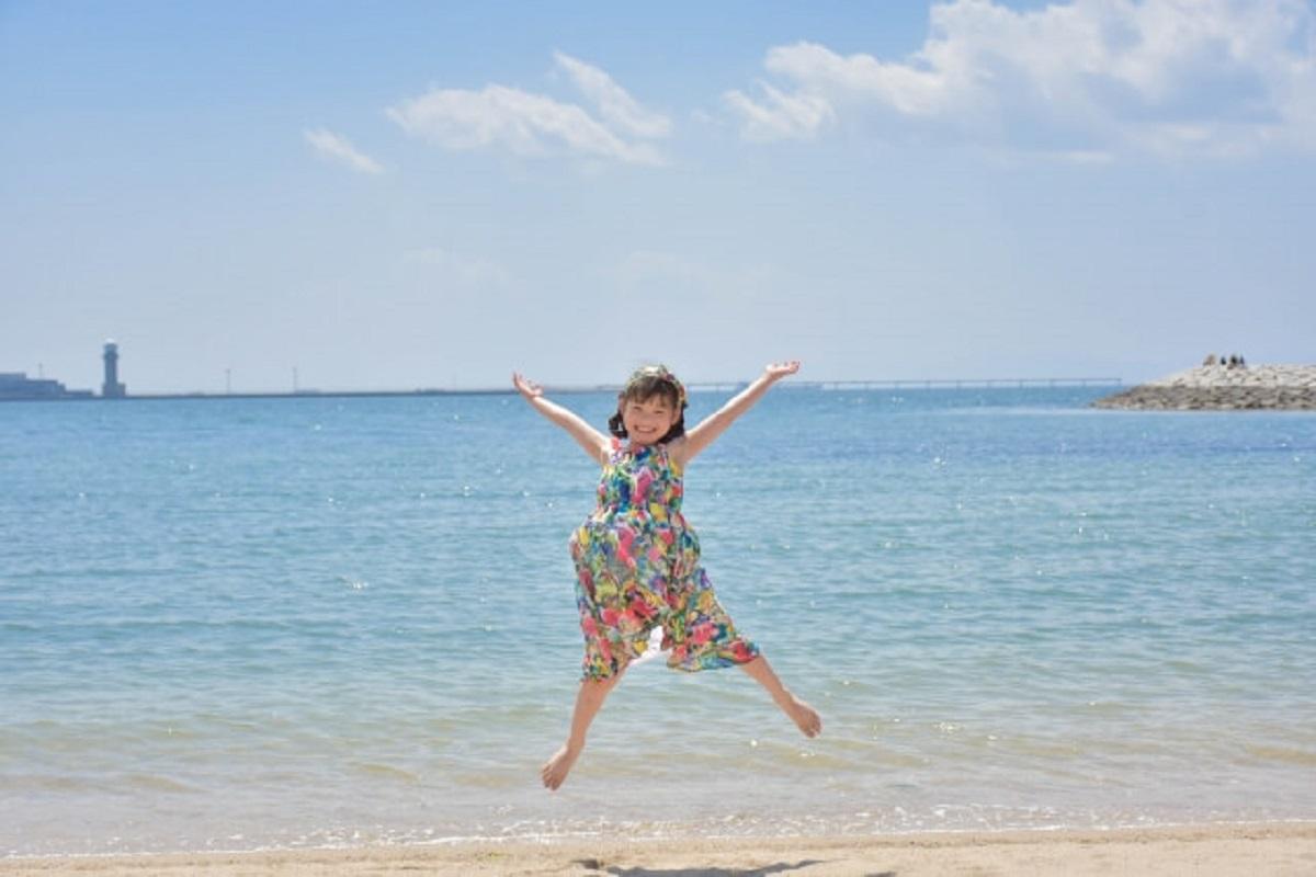 女の子が海の前でジャンプしている画像