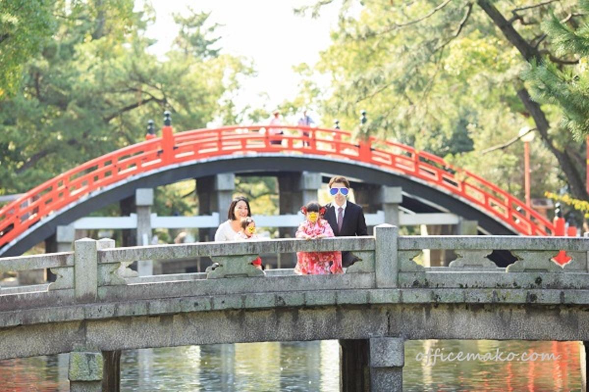 神社の橋の上で家族写真を撮っている写真