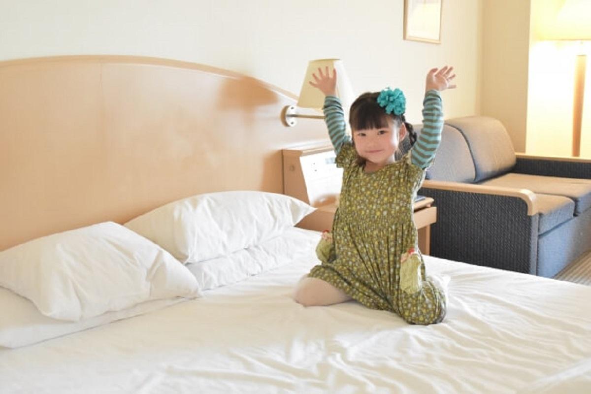 女の子がホテルのベッドの上で手を挙げている画像