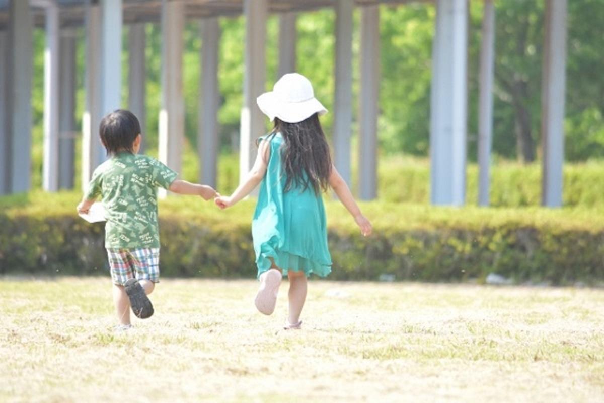 男の子と女の子が手を繋いで走っている画像