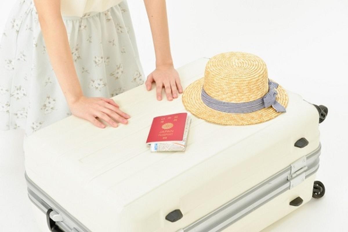 スーツケースを閉める女性の画像