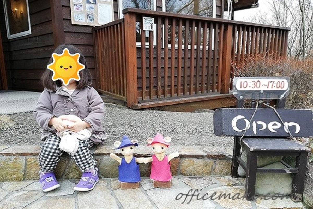 カフェの店先に座っている女の子とぐりとぐらの人形の画像