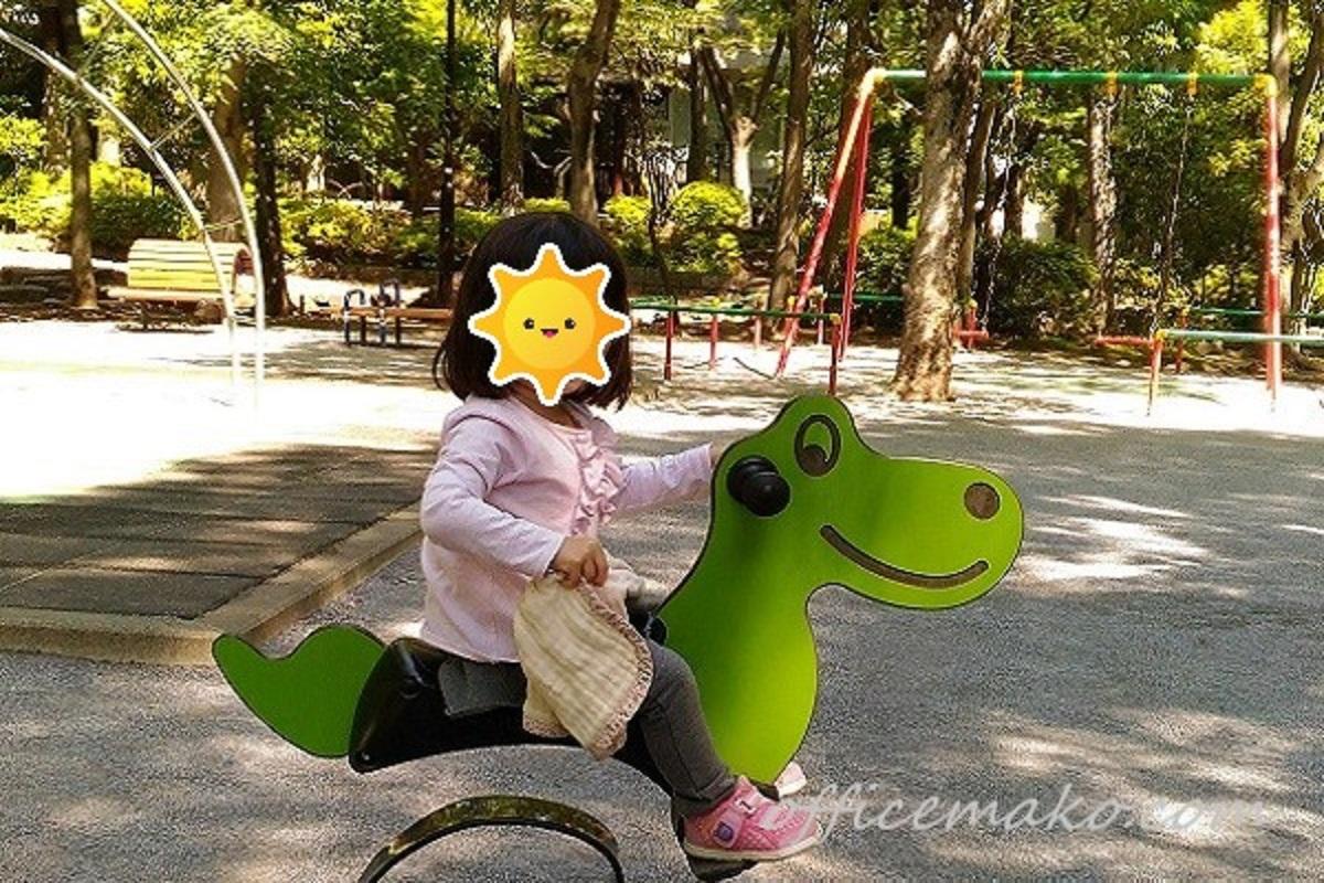 女の子が公園で遊具に乗っている画像