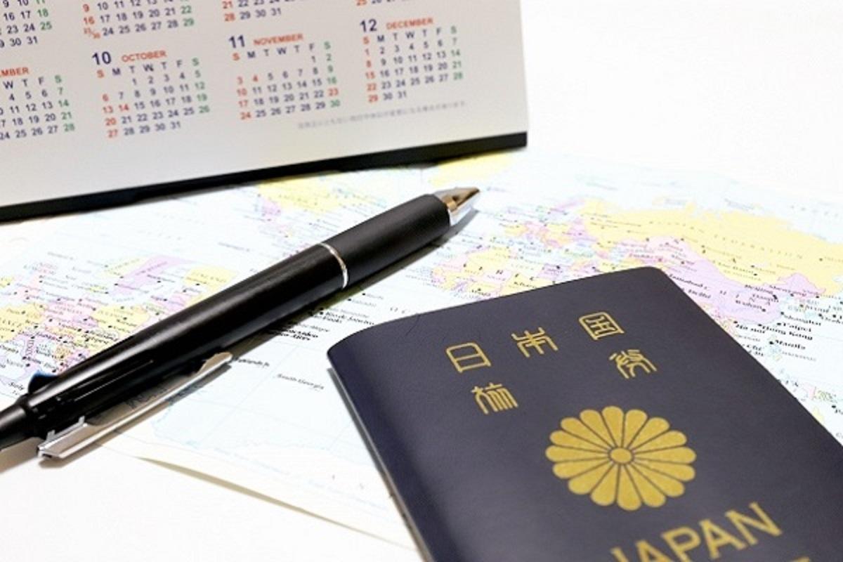 パスポートとボールペンとカレンダーの画像