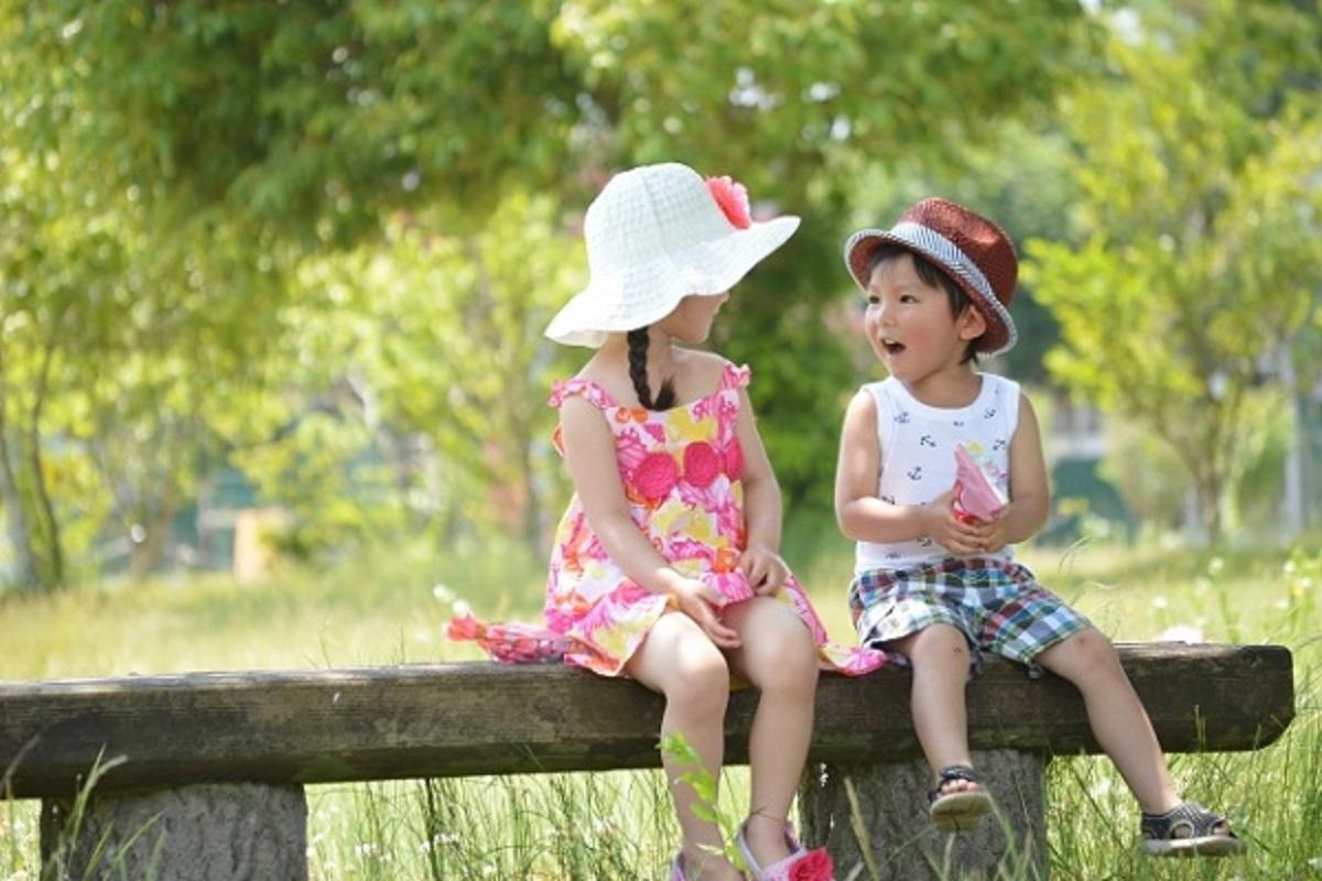 ベンチに座って話す女の子と男の子の画像