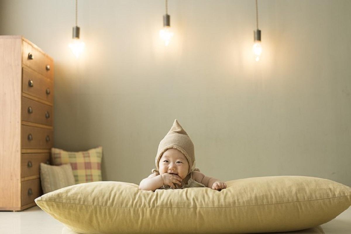 大きなクッションに寝そべっている赤ちゃんの写真