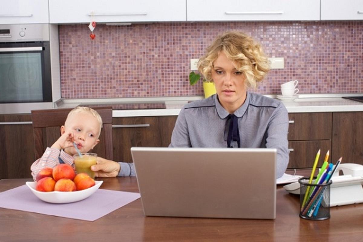 子供のお世話をしながら、パソコンに向かう女性の画像