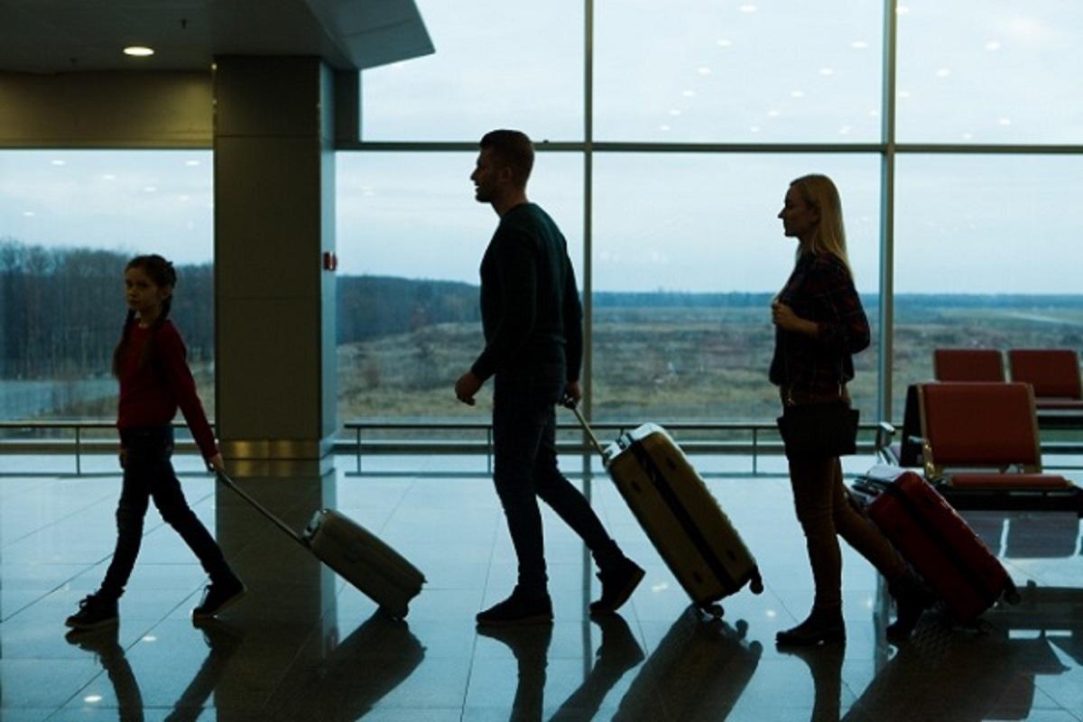スーツケースを引いて空港を歩く家族の画像