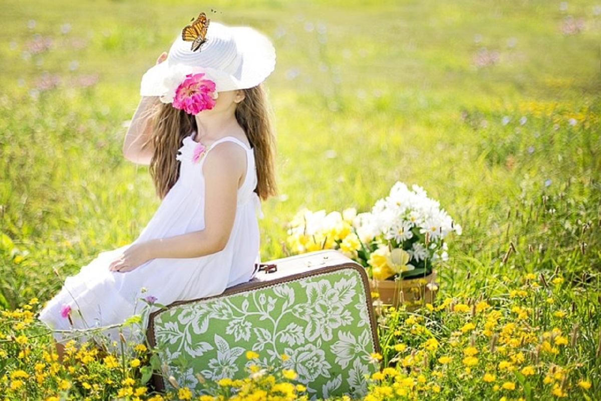 女の子がスーツケースに腰かけている写真
